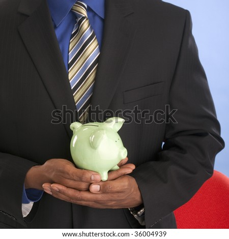 Professional African American man holding a piggy bank - stock photo