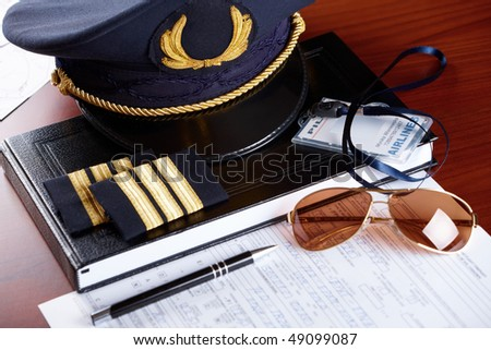 Professional airline pilot hat and id holder with epaulets and sun glasses laying on log book and flight plan. - stock photo