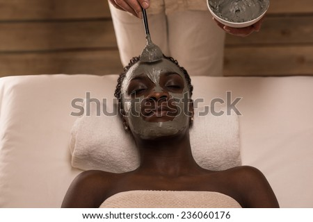 Professional applying mud mask to african woman at spa salon. Top view - stock photo