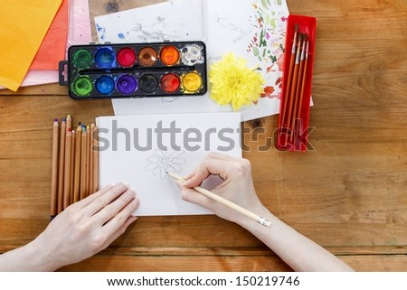 Professional artist painting an chrysanthemum on white sheet of paper. Colorful drawing accessories around.