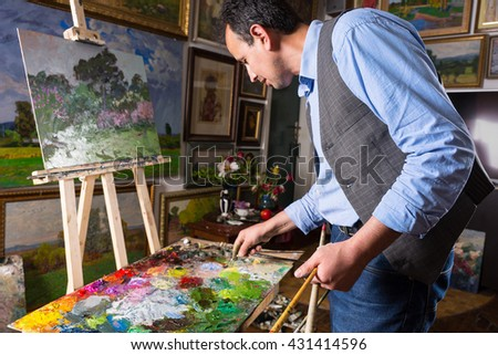 Professional artist working in a gallery or studio selecting a particular hue from a colorful palette of blended oil paints as he works on a painting on an easel - stock photo