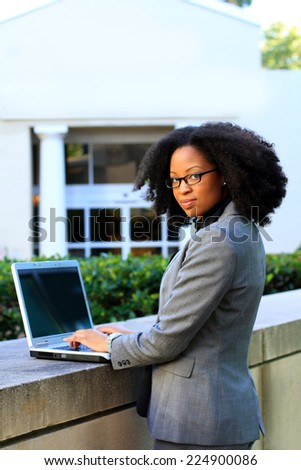 Professional Attractive African American Business Person Woman With Black Hair Typing on Laptop Looking Back Wearing Glasses Looking Back Serious - stock photo