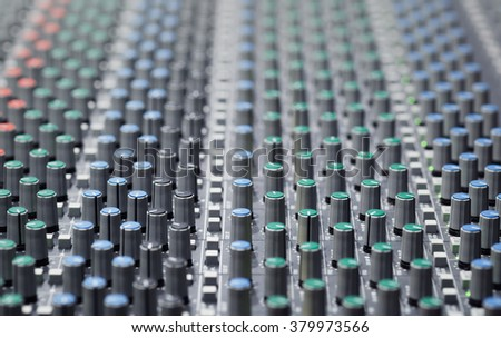Professional audio mixing console closeup with adjusting knobs, buttons equipment ,Music Studio,TV equipment, selective focus - stock photo