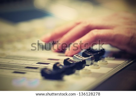 Professional audio mixing console with faders and adjusting knobs - radio / TV broadcasting