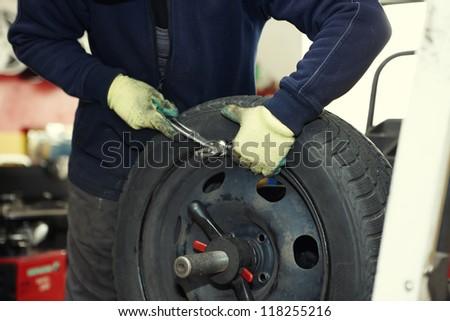 Professional auto mechanic balancing wheel before change it - stock photo