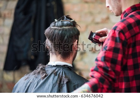 Professional barber styling hair of his client.