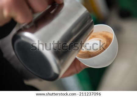 Professional barista pouring milk into the cup of coffee making a pattern - stock photo