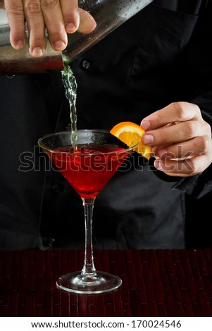 professional bartender pouring a red cocktail in to a martini glass