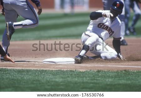 Professional Baseball player sliding into base during game, Candlestick Park, San Francisco, CA - stock photo