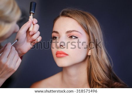 Professional beautician artist applying makeup  on young model. - stock photo