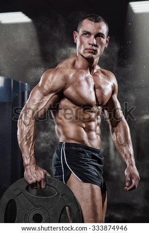Professional bodybuilder with weight disk in gym. Weightlifter with naked torso and the disk in the hands. Fitness male model - stock photo