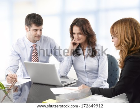 Professional business colleagues working on a laptop in office.