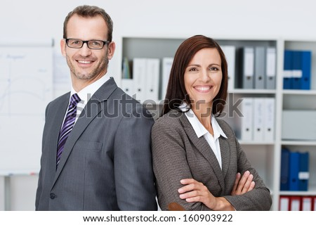Professional business man and woman standing back to back in the office looking at the camera with confident smiles at the success of their partnership - stock photo