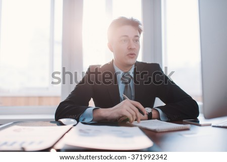 Professional business man at office working at his desk, holding a pen and looking at his laptop