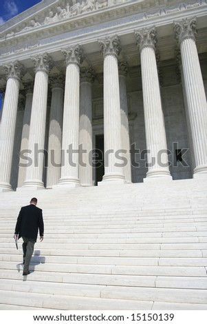 Professional, business man in black suit walking up the steps of the US Supreme Court