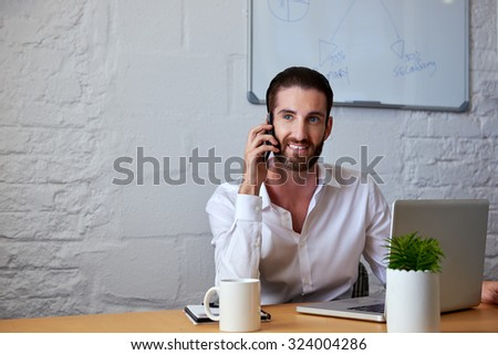 professional business man talking on mobile cell phone to clients in office with laptop computer - stock photo