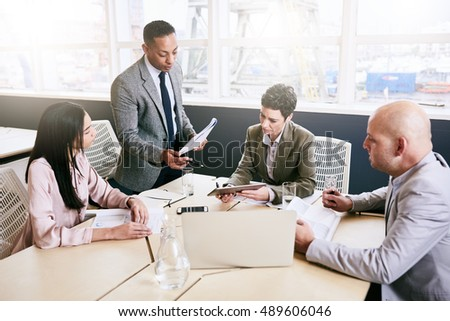 Professional business manager supervising a business meeting taking place between three of his employees during their early morning meeting in the modern conference room.
