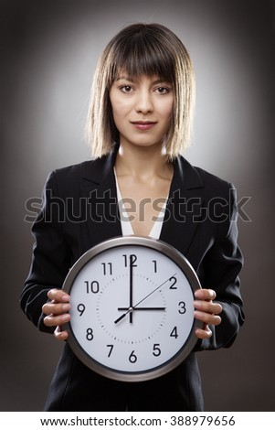 professional business woman holding a large clock - stock photo