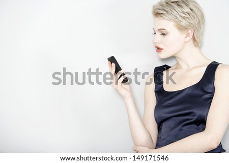Professional business woman on her mobile phone; wearing a smart dress - stock photo