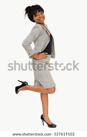 Professional business woman wearing suit skirt high heels leg up smiling happy isolated on gray background - stock photo