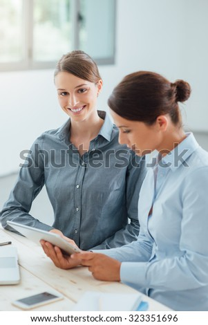 Professional business women sitting at office desk and working together with a digital tablet