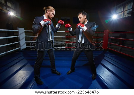 Professional businessmen in suits and boxing gloves standing opposite one another on boxing ring - stock photo