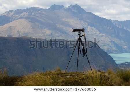 Professional camera with telephoto lens on a tripod during landscape photography outdoor. - stock photo