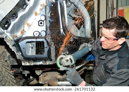 Professional car body repair, grinding welds. - stock photo