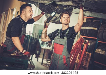Professional car  mechanics  working under lifted car in auto repair service. - stock photo