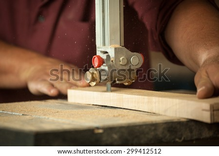 Professional carpenter working with sawing machine in workshop - closeup.