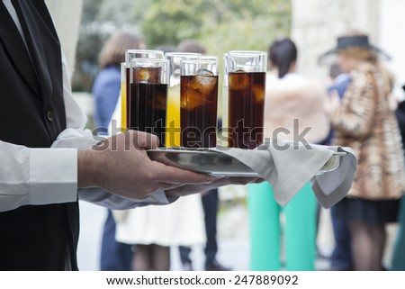 Professional catering service serving drinks to guests. - stock photo