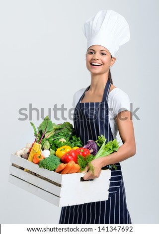 Professional chef holding a crate full of fresh vegetables - stock photo