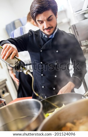 Professional chef in a commercial kitchen cooking a vegetable stir fry over a hob in a copper frying pan as he looks at the camera with a smile - stock photo