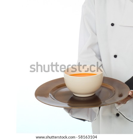 Professional chef in work-wear jacket serving soup isolated on white - stock photo