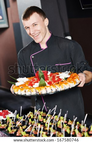 professional chef or waiter with sushi food dish on plates in restaurand cafe - stock photo