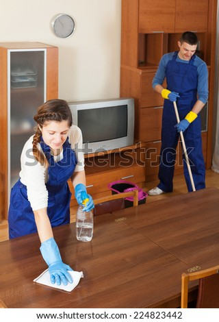 Professional cleaners cleaning furniture and floor