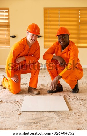 professional construction co-workers doing renovations inside house - stock photo