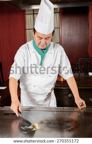 Professional cook. Chef-cook melting butter on a stove getting ready for cooking a dish