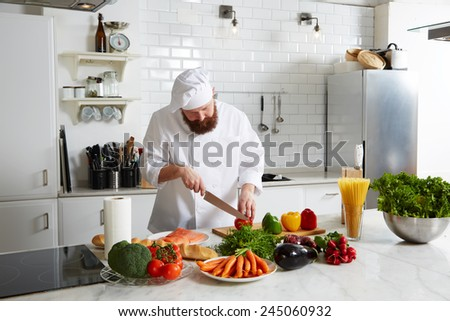 Professional cook cut vegetables in the kitchen, experienced chef making pasta on big kitchen - stock photo