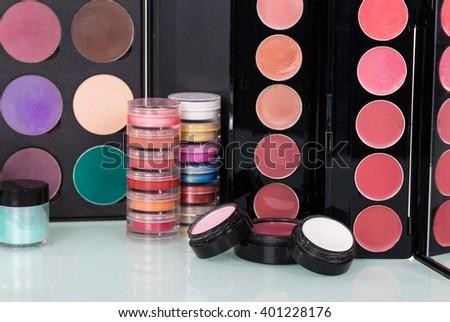 Professional cosmetics: eyeshadow, lip gloss, blush and powder make-up background. - stock photo