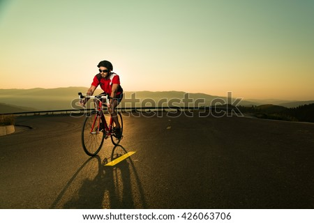 professional cyclist  rides his bike up the hill on the asphalt - stock photo