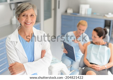 Professional dentist woman patient consultation with assistant at dental surgery - stock photo