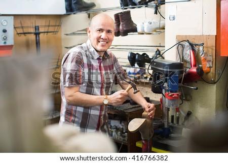 Professional diligent smiling shoemaker heeling footwear on machine in workshop - stock photo