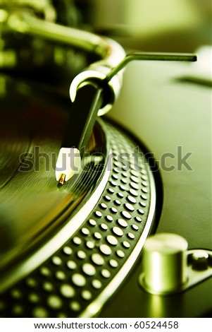 Professional disc jockey turntable plays vinyl record disc with music in bright green lights.needle in focus.Concert dj party poster background.Hip hop style wallpaper