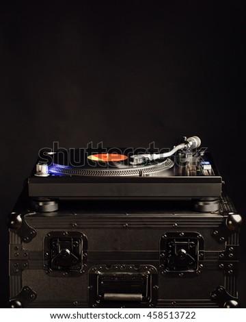 professional dj turntable on flight case, dark background - stock photo