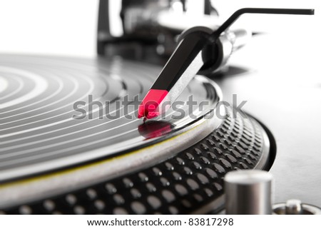 Professional DJ turntable playing analog vinyl record with music. Focus on spherical needle for scratching hip hop music and playing in the night club.Disc jockey audio equipment in focus,isolated