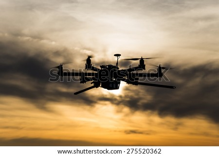 Professional drone flying in the cloudy sunset - stock photo