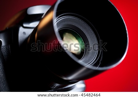 Professional DSLR camera on red background. - stock photo