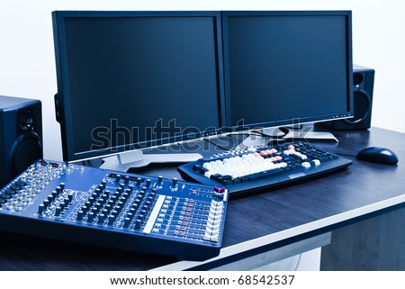 professional editing station with audio mixer and dual monitor setup - stock photo