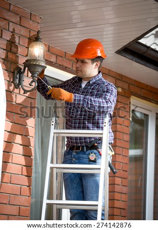 Professional electrician standing on ladder and changing outdoor lamp - stock photo